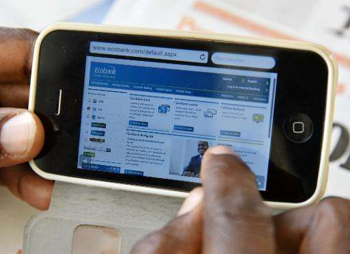 A man looks at a mobile bank website to consult his account on his mobile phone on April 24, 2015 in Abidjan, Ivory Coast