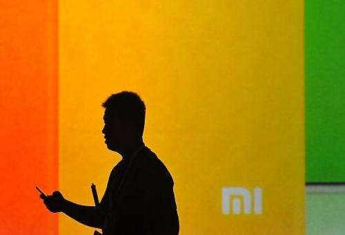 A man looks at his mobile phone as he walks past a screen displaying the Xiaomi logo. AFP Photo / Wang Zhao
