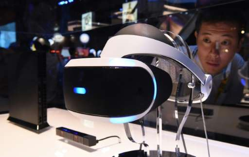 "A man looks at Sony's virtual reality head gear ""PlayStation VR"" during the Tokyo Game Show in Chiba on September 17,"