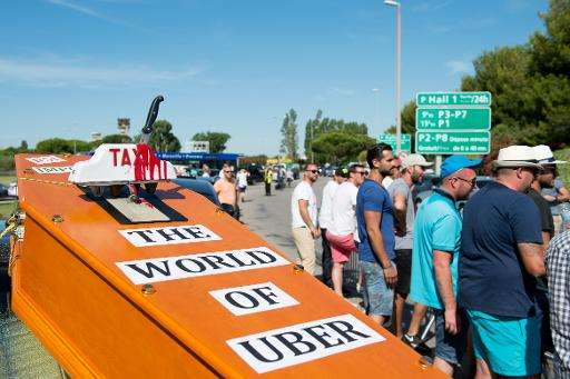A mock coffin is displayed by striking taxi drivers as they  block access to the  Marignane airport near Marseille, southern Fra