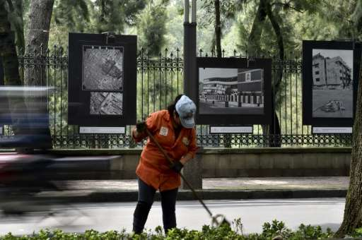 A municipal worker in Mexico City on September 17, 2015  cleans in front of pictures of the damage caused by the September 19, 1
