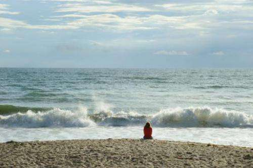An early morning beach goer looks out over the Atlantic Ocean on September 11, 2009 near the Kennedy Space Center in Florida