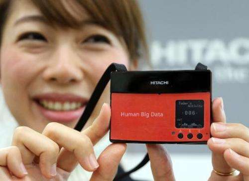An employee from Japanese electronics giant Hitachi shows a wearable sensor aimed at measuring the happiness of workers