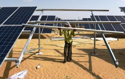 An engineer installs a solar panel at the under-construction Roha Dyechem solar plant in Bhadla, some 225 km north of Jodhpur, i