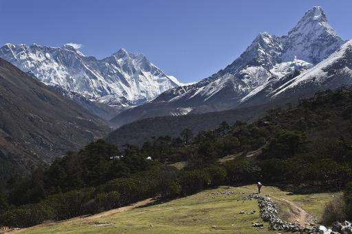 A Nepalese porter carries a load towards Mount Everest and the Himalayas (at left with cloud on top), April 20, 2015