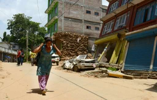 A Nepalese woman carries a load as she walks past destroyed buildings in Chautara on June 30, 2015, following twin earthquakes w