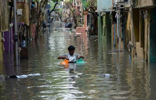 An Indian man carries gas canisters through floodwaters on a street in Chennai on December 4, 2015