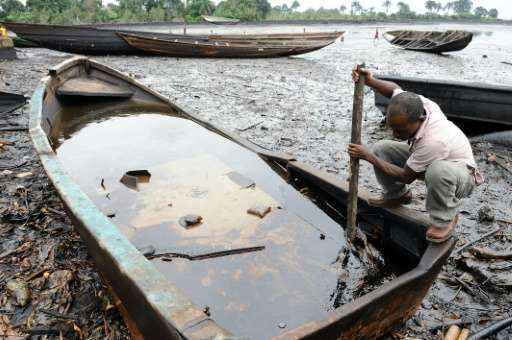 An indigene of Bodo, in Nigeria's Ogoniland region, tries to separate with a stick the crude oil from water in a boat at the Bod