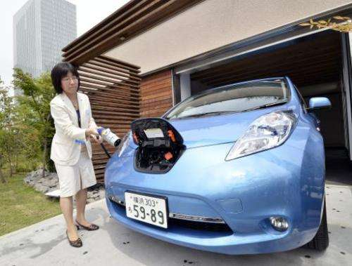 A Nissan employee demonstrates charging one of the country's Leaf electric vehicles using a smart home electricity supply cable