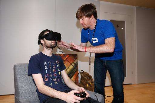 An Oculus emplyoee helps set up the virtual reality head-mounted display Oculus Rift CV1 on a gamer, at the Annual Gaming Indust