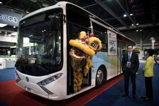 A performer wearing a lion dance costume stands in the door of an electric bus during the opening of the China International New