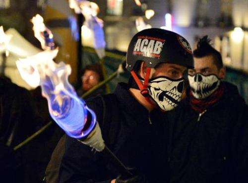 A protestor holds a torch on December 5, 2014 in Nantes during a protest against police brutality following the death of 21-year