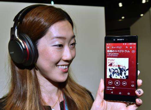 """A Sony employee displays the new smartphone """"Xperia Z4"""" at the company's headquarters in Tokyo on April 20, 2015"""