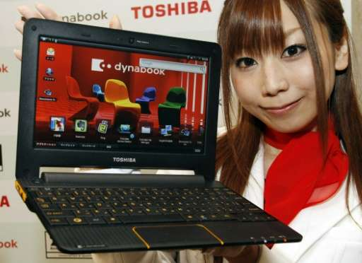 A Toshiba employee displays a Toshiba notebook PC at a Tokyo hotel