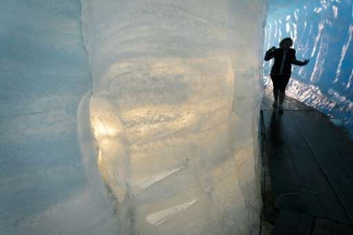 A tourist visits an ice cave inside the Rhone Glacier, which has retreated about 40 metres in length due to melting in the past
