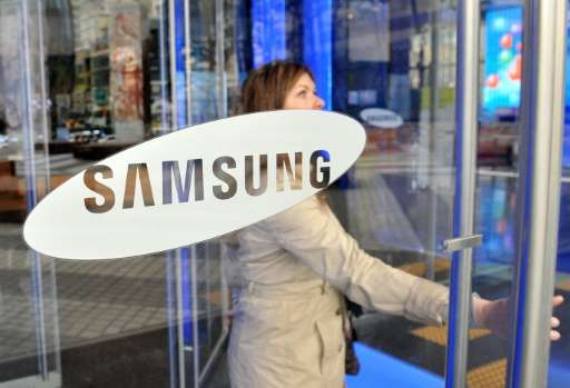 A visitor walks past a logo of Samsung Electronics at the company's headquarters in Seoul on November 22, 2013