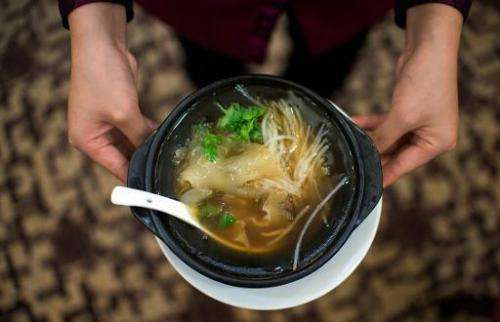 A waitress serves shark fin's soup at a restaurant in Guangzhou, southern China's Guangdong province, on August 10, 2014