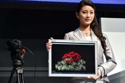 """A woman displays Panasonic's new large tablet """"Toughpad 4K"""" in Tokyo on June 23, 2015"""