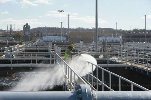 A worker is seen cleaning a wastewater pool at DC Water's Blue Plains plant in Washington, DC