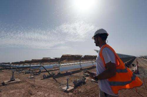 A worker stands in front of a solar power plant in Ouarzazate, Morocco, on October 19, 2014