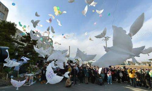 Balloons in the shape of doves are released into the air during a memorial service for the victims of the 2011 quake-tsunami dis