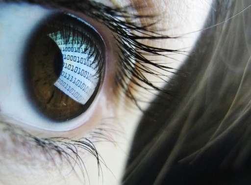 Binary code is reflected from a computer screen in a woman's eye