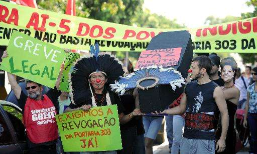 Brazilian natives and employees of the National Indian Foundation protest against the government's decision to authorize actions