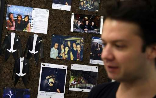 Camilo Paredes, the Colombian-born co-founder and CEO of Hong Kong-based dating app Grouvly, standing in front of a picture boar