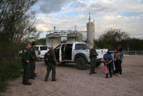 Families of Central American immigrants turn themselves in to US Border Patrol agents after crossing the Rio Grande River from M
