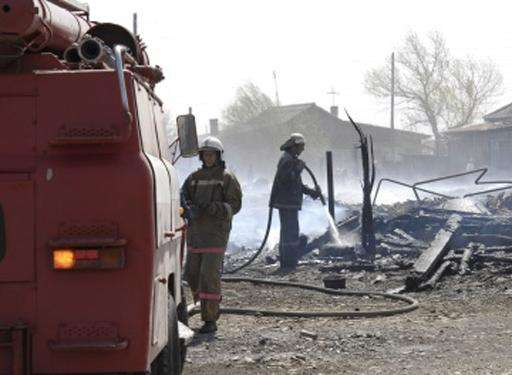 Firefighters extinguish a fire in a village in the Khakassia region of Siberia on April 12, 2015