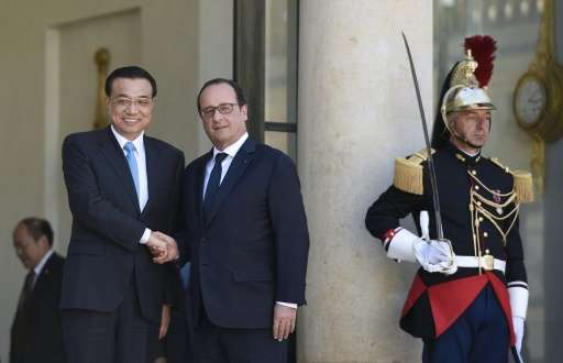 French President Francois Hollande (R) and Chinese Prime minister Li Keqiang shake hands at the Elysee palace, on June 30, 2015,