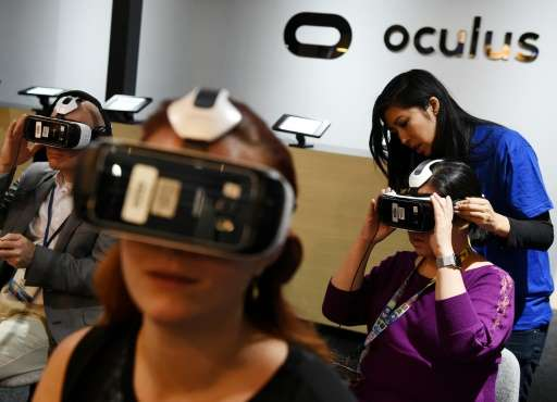 Gamers test a new virtual reality game headset at the Oculus display at the Electronic Entertainment Expo in Los Angeles, Califo