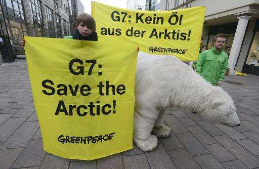 """Greenpeace activists pose with a mockup of a polar bear and with banners reading """"G7: Save the Arctic!"""" and """"G7:"""