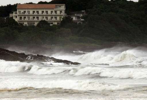 High waves crash into the coast at Hyuga in Miyazaki prefecture, Japan's southern island of Kyushu on July 16, 2015 after typhoo