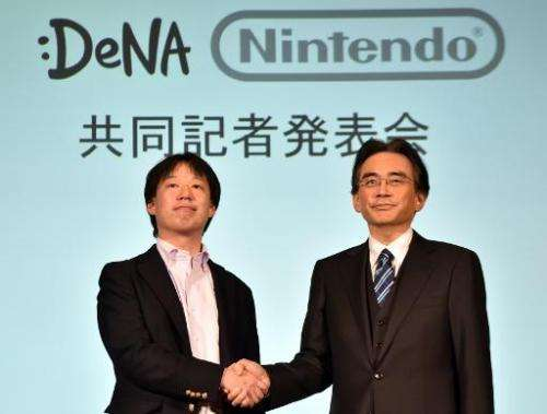 Japan's video game giant Nintendo president Satoru Iwata (right) shakes hands with Japanese online game operator DeNA president