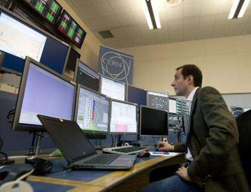 LHC operator Mirko Pojer watches screens at the CERN Control Center (CCC) in Meyrin, near Geneva
