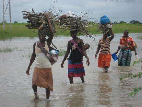 Local women wade through floodwater on the outskirts of Chokwe, near the Limpopo river, Mozambique, on January 26, 2011