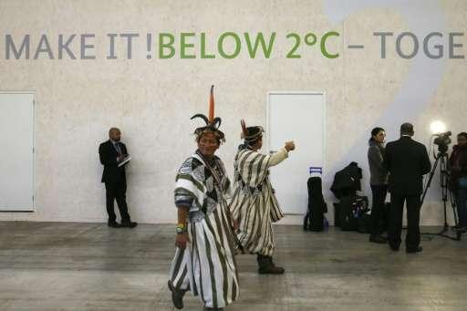 Lyndon Pishagua Chinchuga, a representative of the indigenous peoples of the Peruvian Amazon, walk past a stand at COP 21, the U