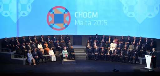 Malta's Prime Minister Joseph Muscat (R) delivers a speech during the opening ceremony of the Commonwealth Heads of Government M