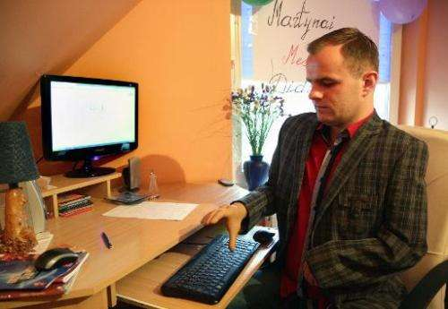 Martynas Girulis uses his new bionic hand to type on a keyboard at his home in Pagegiai, Lithuania