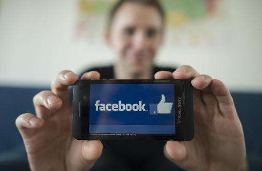 Max Schrems displays Facebook's logo with his smartphone during an interview with AFP in Vienna, Austria on April 7, 2015