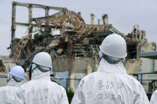 Members of a Japanese government panel inspect the damaged building housing reactor number three at the Fukushima Dai-ichi nucle