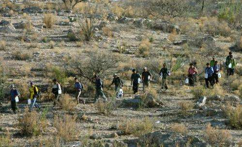 Mexican immigrants walk in line through the Arizona desert near Sasabe, Sonora state, in an attempt to illegally cross the Mexic