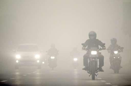 Motorists travel under a heavy blanket of haze in Palangkaraya, on Indonesia's Borneo island, on October 12, 2015