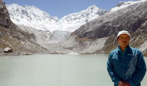 Mountan guide Saul Luciano Lliuya stands at a lagoon formed under the almost disappeared ice and snow mass on the Churup glacier