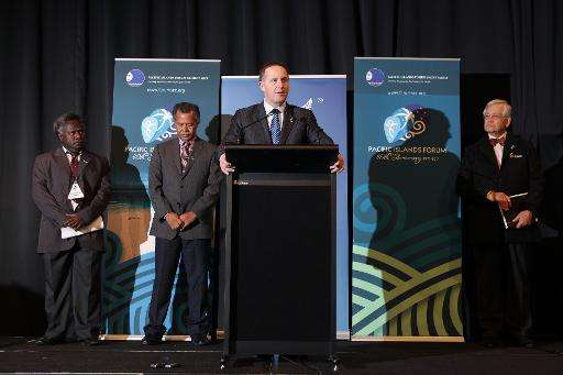 New Zealand's Prime Minister John Key (C) speaks to the press during the annual Pacific Islands Forum (PIF) summit, in Auckland,