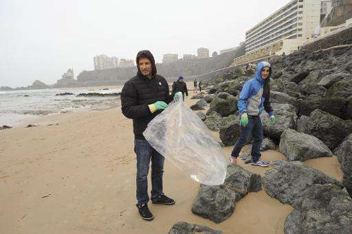 People collect waste  on a beach in Biarritz, France during the launch of a weekend of voluntary cleanup, called Initiatives Oce