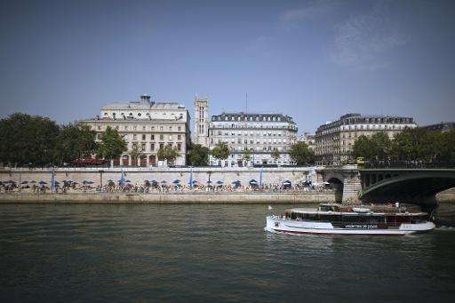 People enjoy the sun at the Seine riverside as on August 19, 2012 in Paris during Paris-Plages, an event which sees the river ba