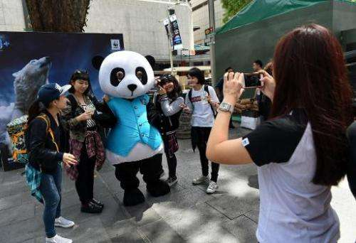 People in Singapore on March 12, 2915 pose with a WWF (World Wide Fund For Nature) panda mascot promoting Earth Hour