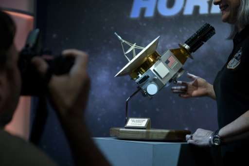 People pose with a model of the New Horizons probe at the Johns Hopkins University Applied Physics Laboratory July 14, 2015 in L